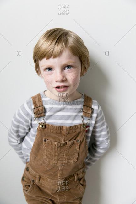 Portrait of little boy wearing corduroy overalls