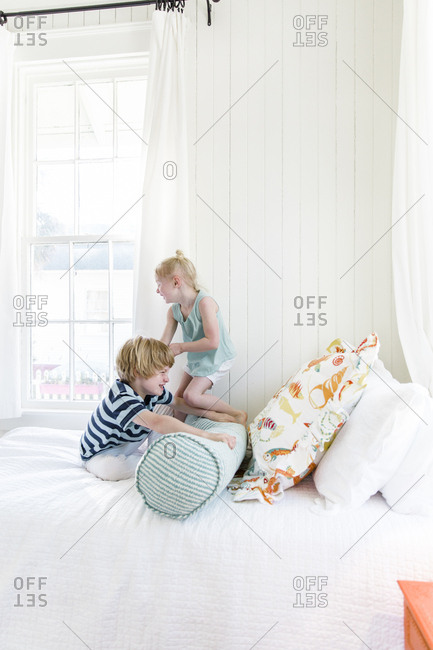 Two kids in a bright room playing on a bed