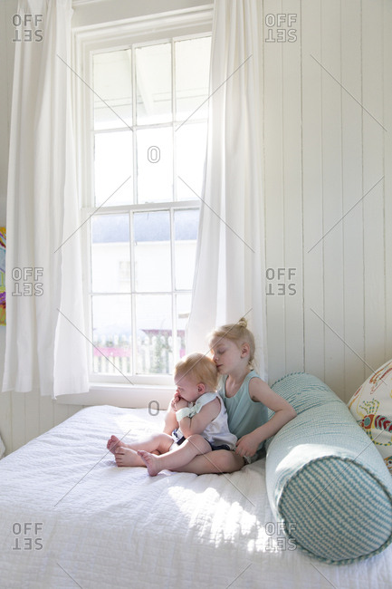 Two little girls sitting on bed together