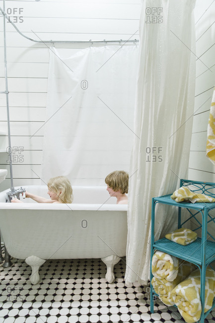 Two kids bathing in claw foot tub