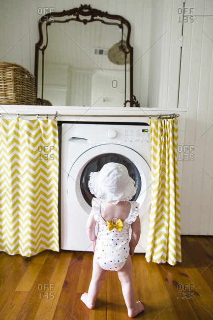 Baby girl in bathing suit in front of dryer