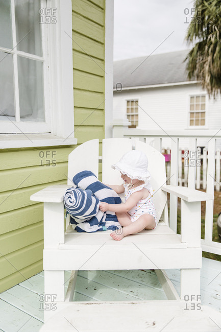 Baby girl in bathing suit sitting on Adirondack chair