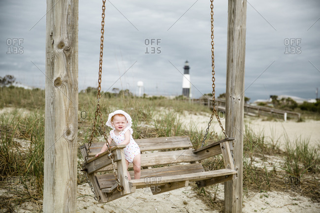 Baby standing on wooden swing on Tybee Island