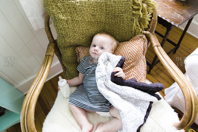 Baby sitting in chair with bottle