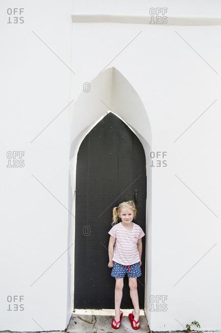 Girl standing in front of black church door