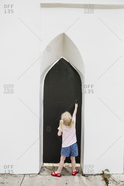 Girl opening black church door