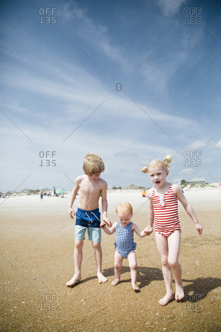 Three siblings holding hands on a beach in Saint Augustine, Florida