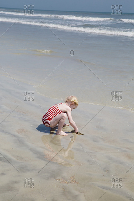 Little girl playing on the ocean shore in Florida