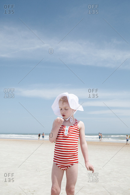 Little girl wearing hat and striped suit on a beach