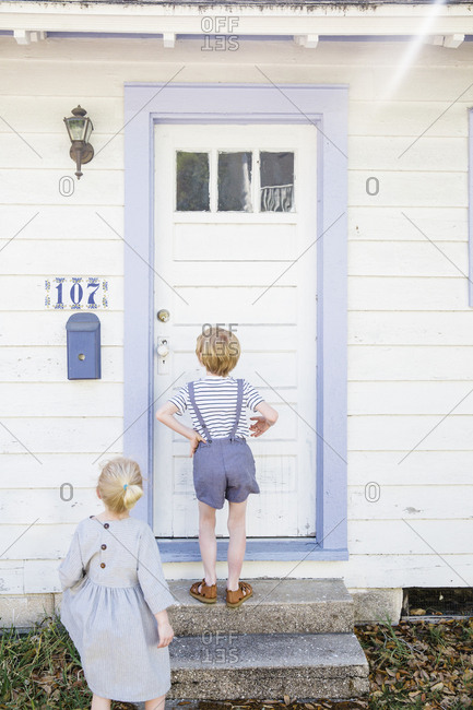 Two kids standing in front of a white door with blue trim