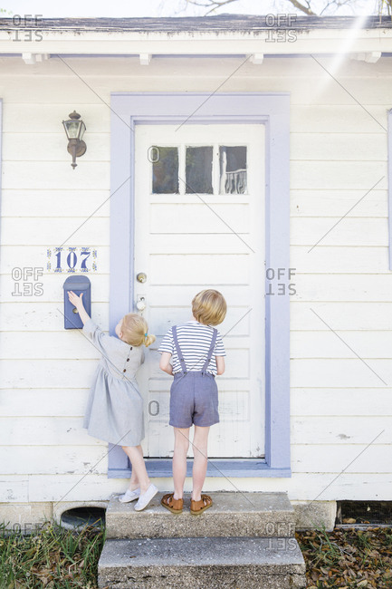 Kids standing in front of a white door with blue trim and touching mailbox