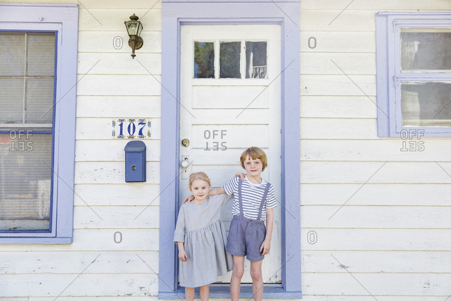 Siblings standing in front of a white door with blue trim