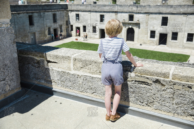 Boy overlooking courtyard in Castillo de San Marcos
