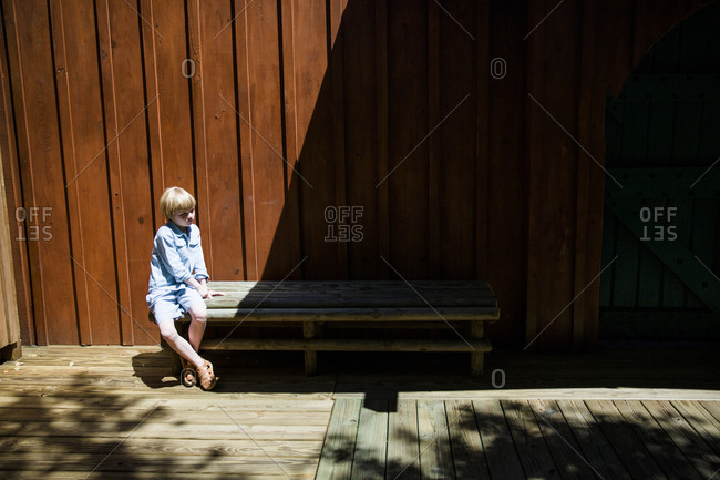 Boy sitting on wooden bench in sunlight looking away