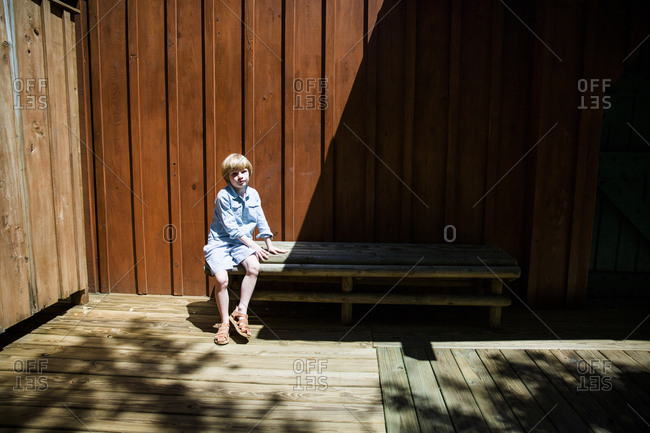 Boy sitting on wooden bench in sunlight