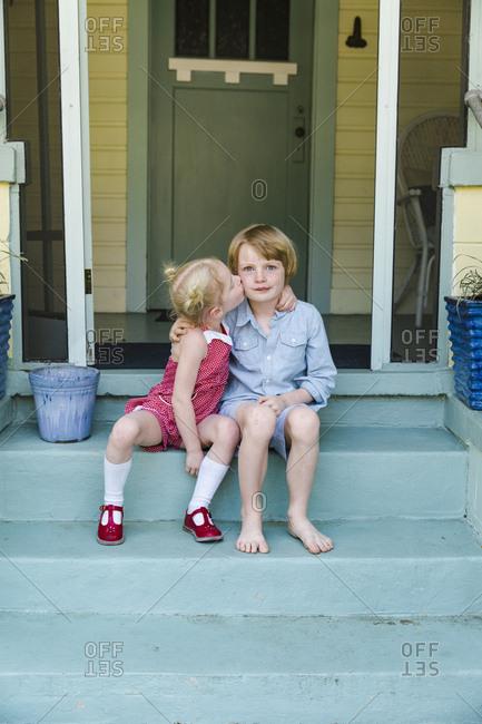 Little girl kissing brother's cheek on steps