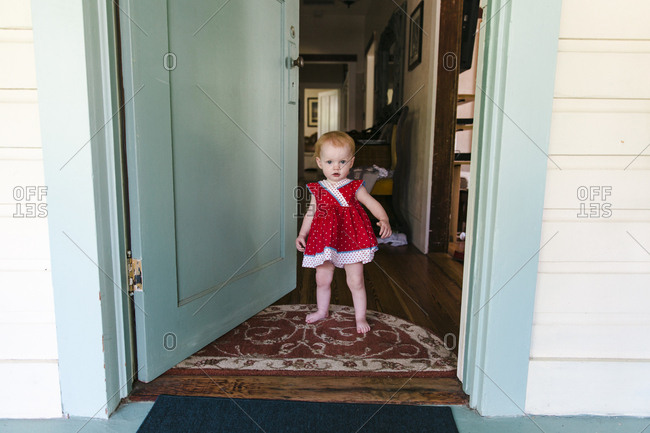 Baby girl standing by blue front door