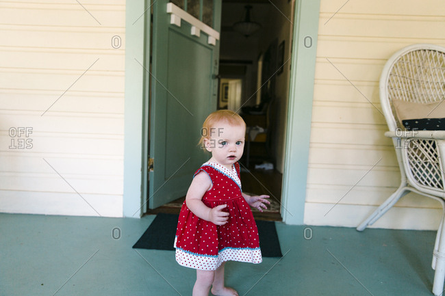 Baby girl standing by blue front door on porch