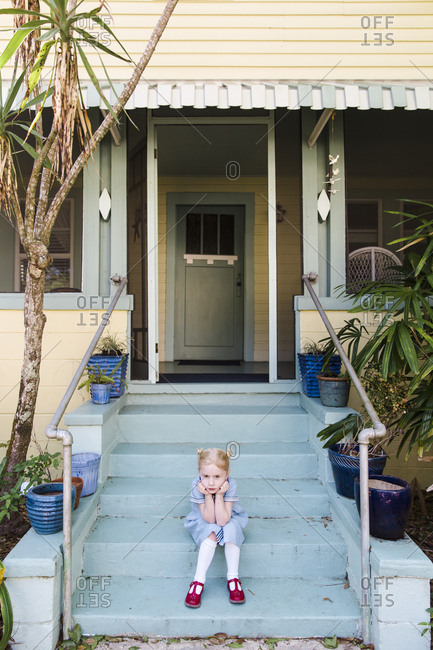 Girl sitting on front steps pouting