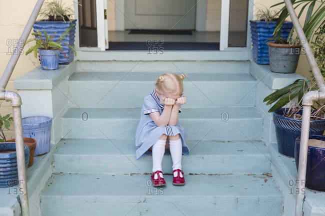 Sad girl sitting on front steps