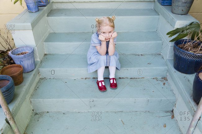 Little girl sitting on front steps pouting
