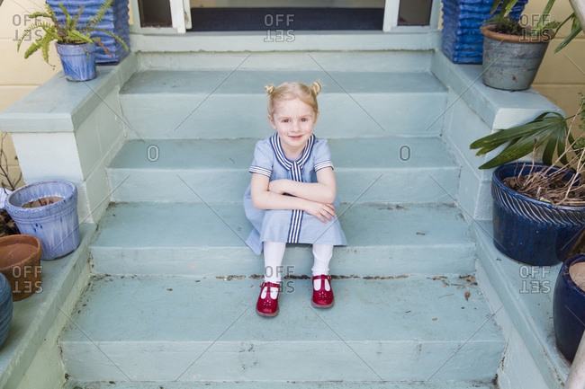 Happy little girl sitting on front steps