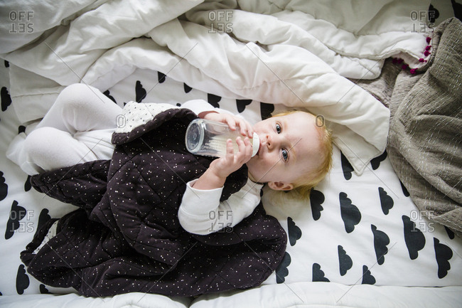 Baby lying in bed drinking bottle