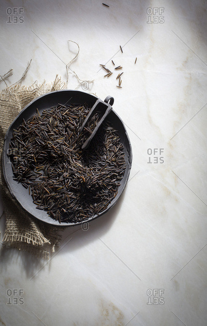 Wild rice in a ceramic black ceramic plate on a marble table on top view