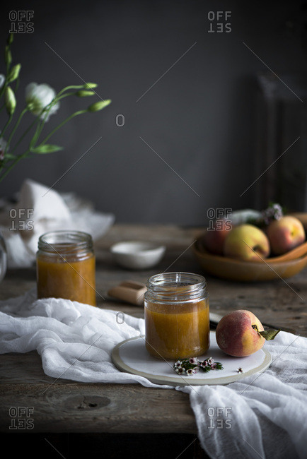 Homemade Peach jam and fresh peaches on a table
