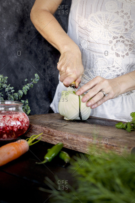 Women prepping for Quick Pickled Veggies. Photographed on a black wooded background.