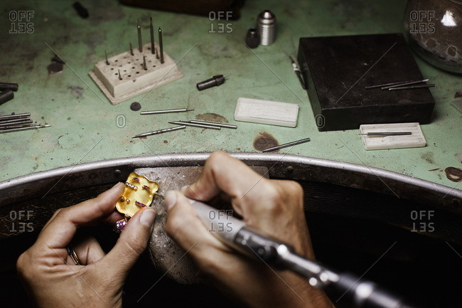 Person making jewelry with machine