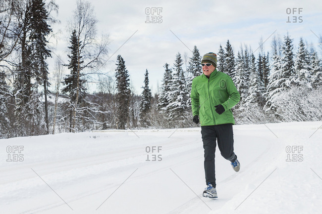 Mature adult male running in winter on snow covered road