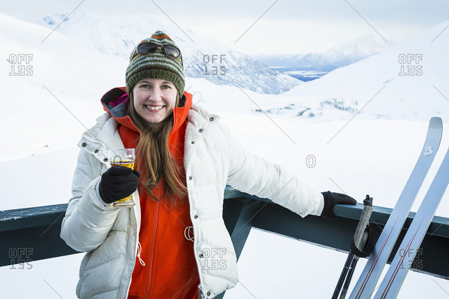 Young adult woman relaxing on a deck, having a beer while taking a break from cross country skiing