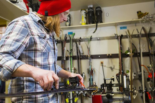 Male ski shop employee preparing to tune skis
