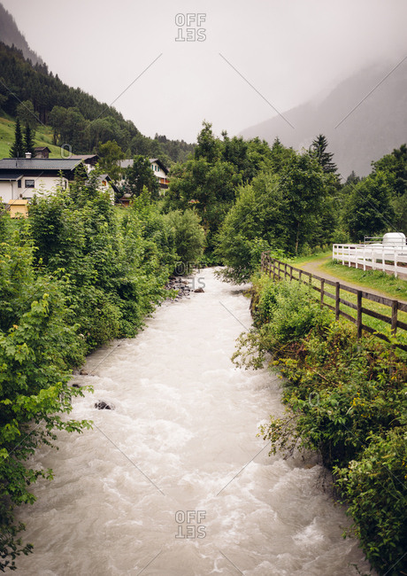 Charming image of creek running through the village of Brand in Austria during cloudy weather.
