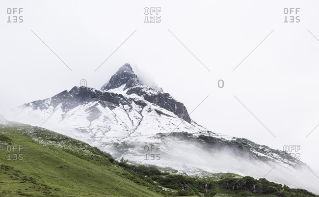 Moody image during stormy weather of snowy and rocky peak in the Arlberg region of Austria.