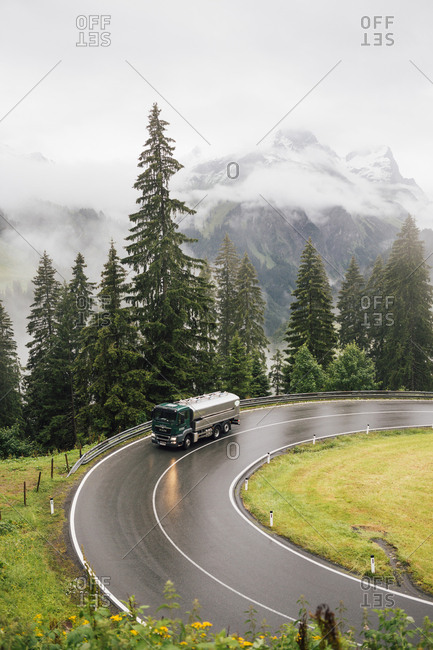 Schroecken, Vorarlberg, Austria - July 14, 2016: truck driving through turn in alpine landscape in Austria during bad weather.