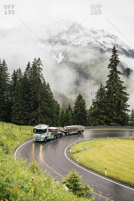 Schroecken, Vorarlberg, Austria - July 14, 2016: truck driving through turn in alpine landscape in Austria during bad weather.