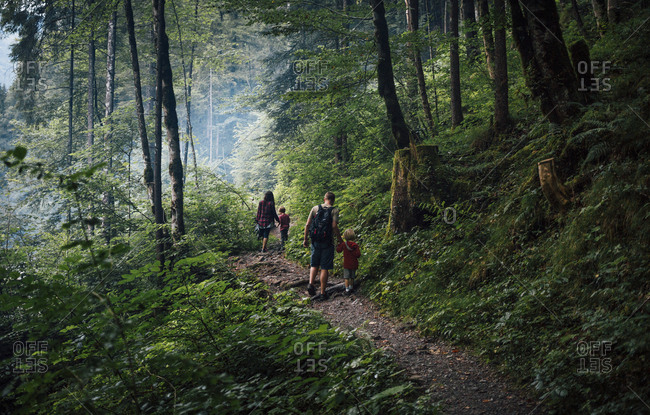 Moody image of young family of four walking on trail in mountainous landscape in Austria.