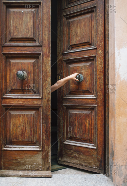 Beautiful wooden door with arm of a kid reaching out to pull it open.