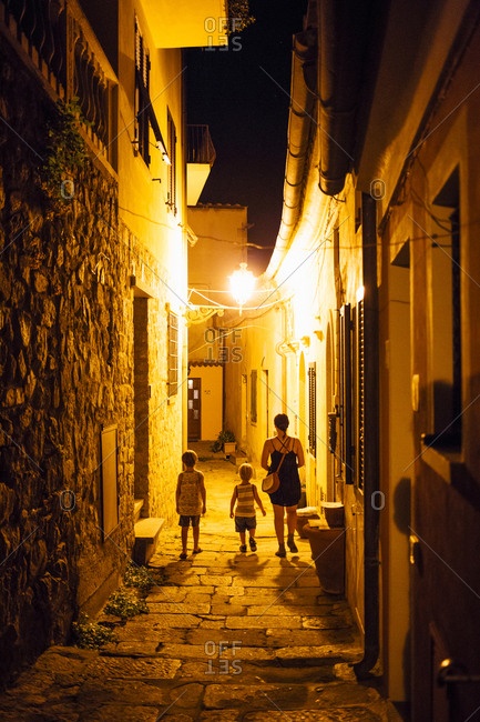 30 something brunette mother and two blonde sons explore charming alleys in Italian village at night.
