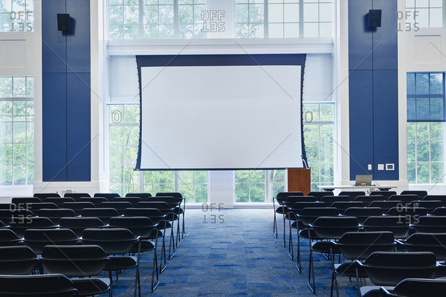 Cathedral style lecture room with rows of chairs and a projector screen.