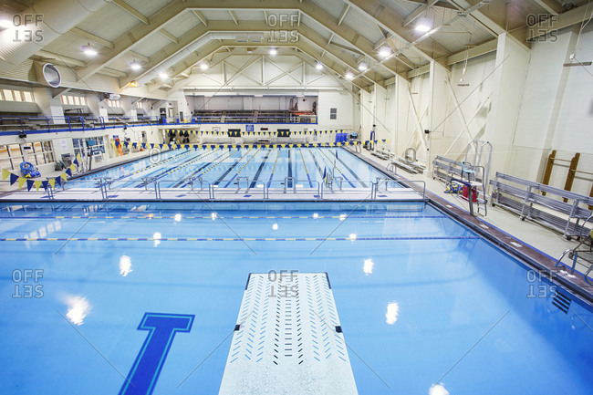 Indoor swimming pool view from a diving board, for school sport programs and swim competitions.