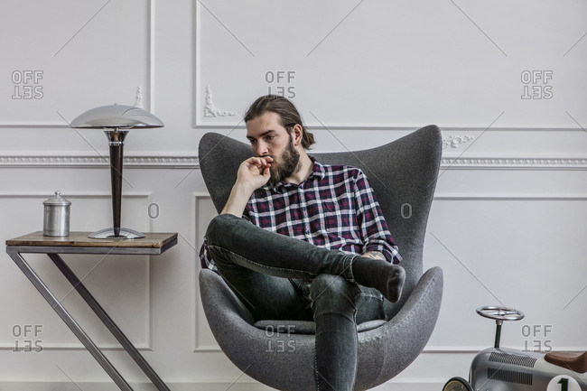 Young hipster sits in a fancy designer chair pondering, thinking