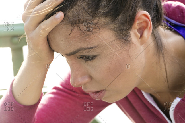 Young women sweating with one hand on head looking tired