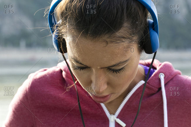 Young women wearing headphones and running top catching her breath and sweating