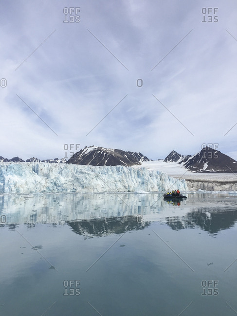 Tourists explore Lilliehook Glacier in Svalbard by zodiac raft.