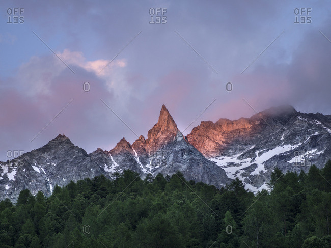 Early evening sun on the Arolla mountain range in Switzerland with Pine trees in the foreground.