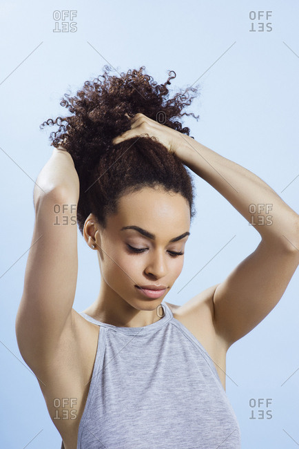 Young African American woman with fresh skin tying up her curly hair
