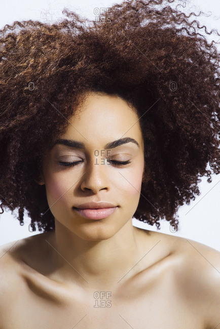 Young African American woman with curly hair, fresh skin and eyes closed